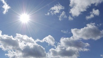bright sun shining in blue sky with white clouds