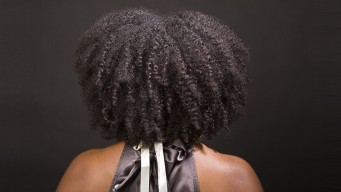 the back of an African American woman's head showing her curly afro and bare shoulders