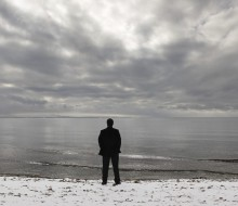 A man stands alone facing the ocean with a cloudy sky above