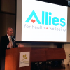 Sean DeYoung, CEO of Allies for Health + Wellbeing, unveils the new logo.
