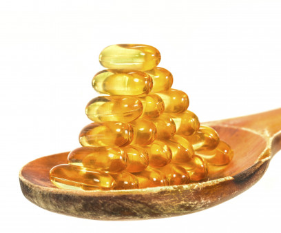Vitamin D Capsules on wooden spoon